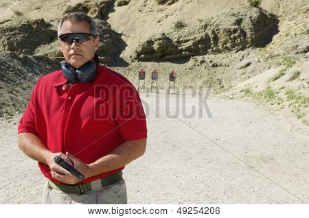 Man holding hand gun at firing range portrait