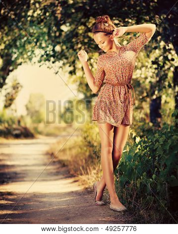 Beauty Romantic Girl Outdoor. Beautiful Teenage Model Dressed in Fashionable Short Dress Posing Outdoors in Sun Light. Full Length Portrait. Toned in warm colors. Fashion Look