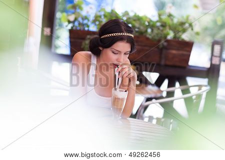 Young Girl Drinking Coctail In A Cafe