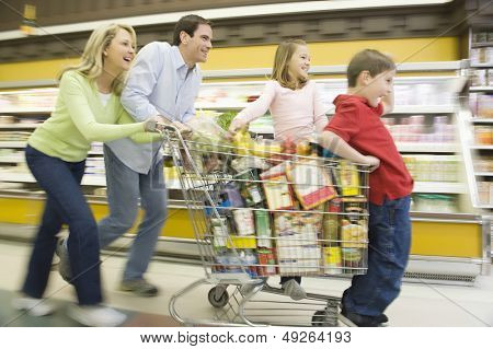 Full length side view of family of four running with full shopping trolley