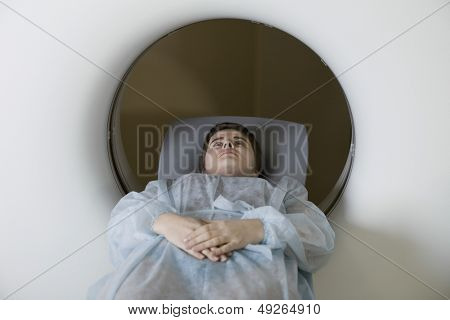 Young woman lying in front of CAT scan machine