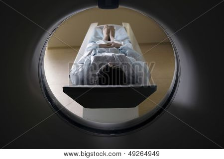 Full length of a woman lying in front of CAT scan machine