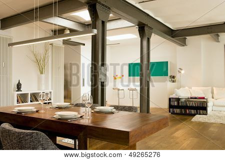 Dining room with view of bar and living area in the background at modern home