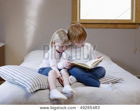 Full length of two young sisters reading book on a single bed