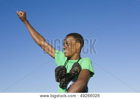 African American man with football boots round his neck and an arm raised against clear blue sky