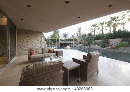 View of an outdoor room by swimming pool of a modern home