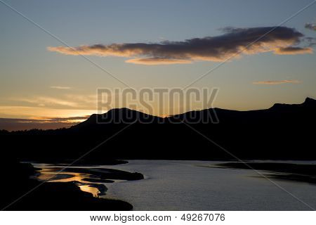 Stunning Silhouette Landscape Of Setting Sun Reflecting In Water And Making It Appear Golden
