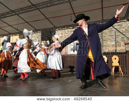 DOMAZLICE CZECH REPUBLIC - AUGUST 10: The Folklore Ensemble Usmev (Smile) dressed in traditional Czech (Pilsen) garb dancing and singing on The Chodske slavnosti medieval market on August 10, 2013.