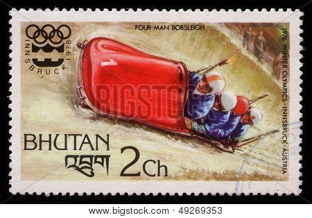 BHUTAN - CIRCA 1976: A stmp printed in Bhutan shows four man bobsleigh at the Olympic Winter Games in Innsbruck, circa 1976