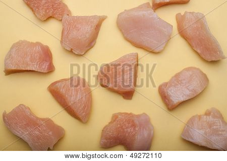 Raw chicken chunks on yellow surface