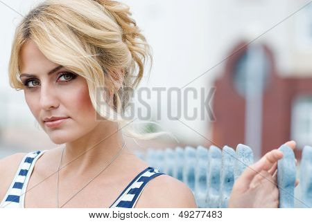 Portrait Of A Beautiful Girl On The Street. The Background Is Blurred.