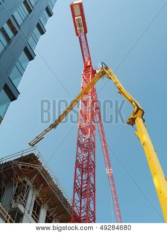 Highrise buildings under construction and two jib cranes over clear blue sky