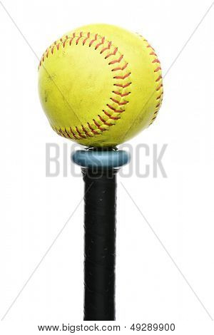 A used yellow softball resting on the knob end of an aluminum bat. Vertical format isolated on white.