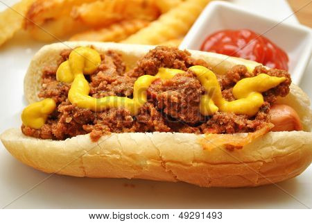 Chili Dog and Mustard with Catsup and French Fries in the Background