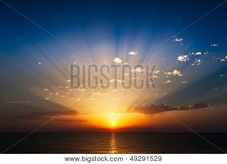 Perfect sunrise on the sea, with radiant rays of sun over a warm colourful horizont.