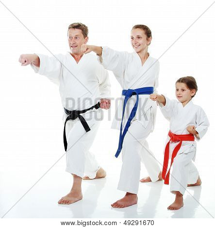 Family sportsmen two sisters with her father in a kimono beat punch arm