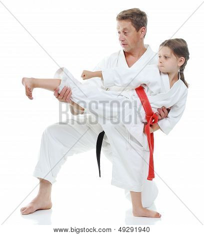 Girl learns to beat  kick leg on white background
