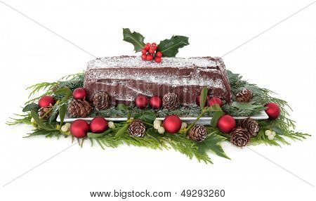 Christmas chocolate yule log cake with red bauble decorations, holly, mistletoe, snow, pine cones and winter greenery over white background.