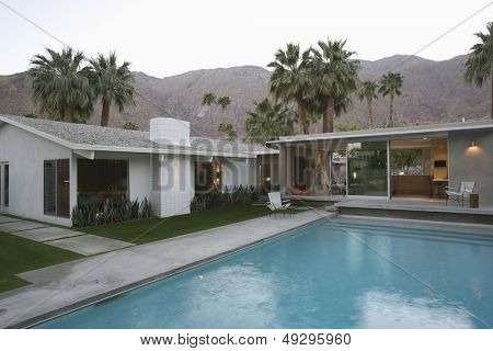 View of swimming pool and modern home exterior against mountains