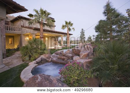 View of an outdoor Jacuzzi and modern house exterior against clear sky