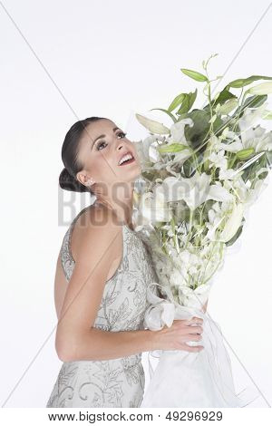 Side view of a young woman in evening dress accepts a bouquet of white flowers against white background