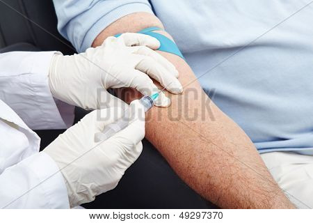 Man giving blood donation with syringe in his arm