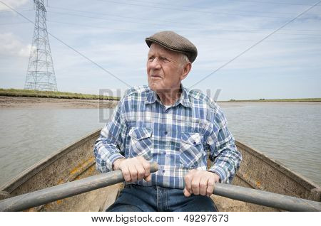 Senior man rowing a boat on a reservoir
