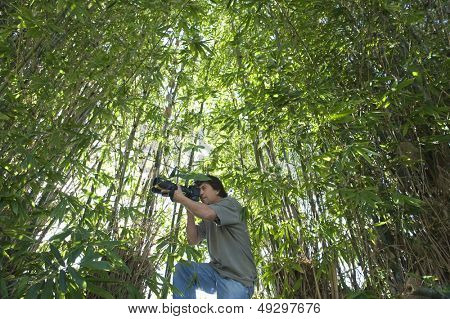 Low angle view of a male photographer adjusting camera lens in bamboo forest