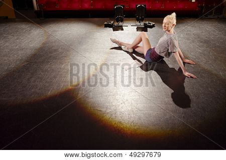 Full length side view of a young woman relaxing on stage