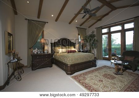 View of a spacious bedroom with beamed ceiling and patio doors
