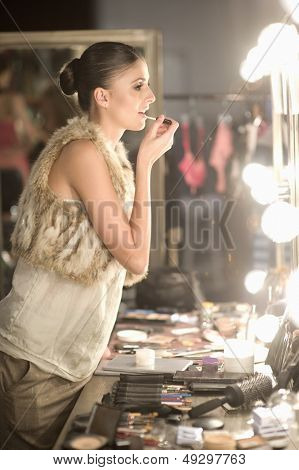Side view of a young woman applying lipgloss in dressing room mirror