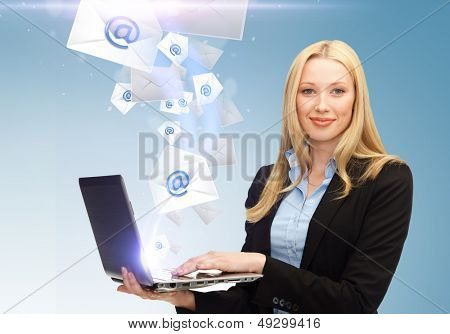 business, communication and internet concept - businesswoman holding laptop with email sign