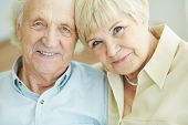 stock photo of retired  - Portrait of senior couple looking at camera with smiles - JPG