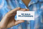 stock photo of courtesy  - A person holding a white card with the words We build Relationships - JPG