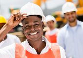 stock photo of real-estate-team  - Happy construction worker at a building site wearing a helmet - JPG