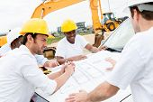 stock photo of engineering construction  - Group of civil engineers working on a construction and looking at blueprints - JPG