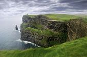stock photo of leprechaun  - Stormy sky over Cliffs of Moher covered in lush grass in Ireland - JPG