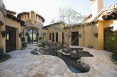 stock photo of hacienda  - Paved courtyard garden with pond in house against clear sky - JPG