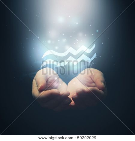 Female Hands Opening To Light And Holding Zodiac Sign For Aquarius.