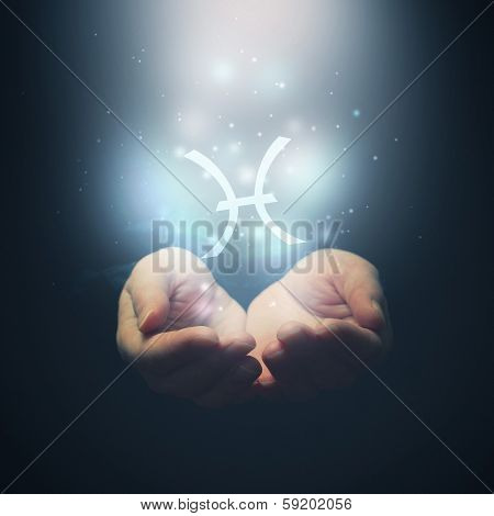 Female Hands Opening To Light And Holding Zodiac Sign For Pisces