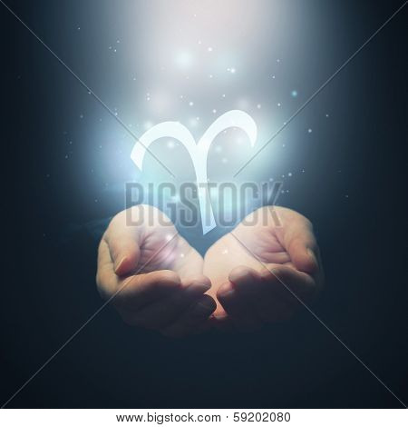 Female Hands Opening To Light And Holding Zodiac Sign For Aries
