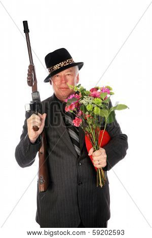 A 1920's era gangster in a pin stripe suit holds his Thompson Sub machine Gun while isolated on white with room for your text