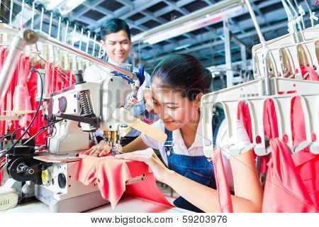 Asian Seamstress or worker in a textile factory sewing with a industrial sewing machine, she is very accurate, the manager looking pleased at her work