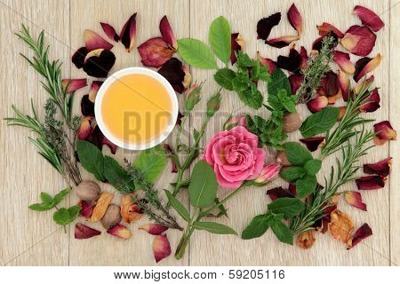 Honey, herb and rose flower ingredients for magical love potions over oak wood  background.