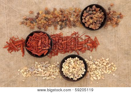 Frankincense, myrrh and sandalwood incense selection over distressed paper background.