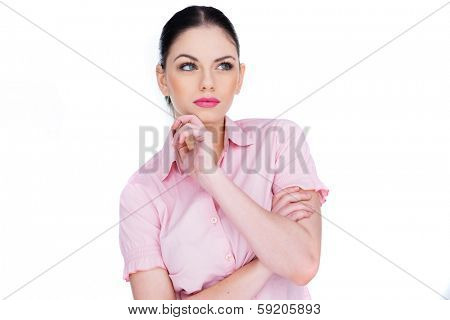 Attractive young woman deep in thought standing with her hand to her chin staring upwards with a slight frown as she tries to remember something, isolated on white