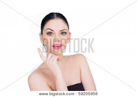 Beautiful woman with a bright inspirational idea raising her finger with a look of astonishment as the solution to a problem suddenly dawns on her