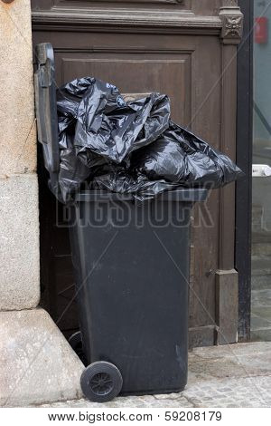 trash or garbage bins for household waste in front of a residential building