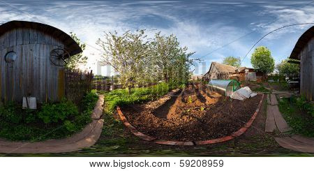 Spherical, 360 degrees panorama (equiregtangular projection) of a spring blooming garden in a village at sunset.