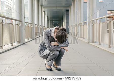 Business woman feel helpless and sadness and squat on ground in city.
